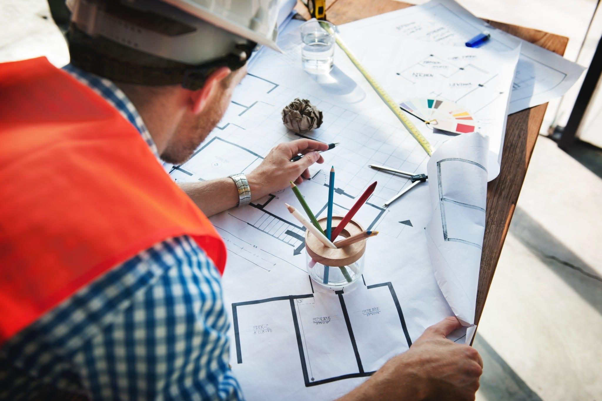 Construction worker looking over blueprints
